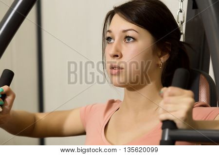 young woman is engaged in sports and gymnastics in the gym.