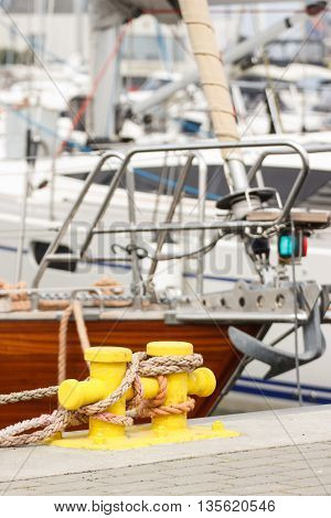 Blue rope and yellow mooring bollard in port with yacht in background detail of yachting
