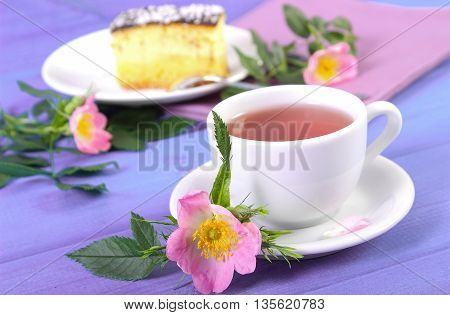 Cup Of Tea With Cheesecake And Wild Rose Flower On Purple Boards