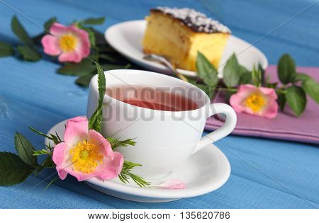 Cup Of Tea With Cheesecake And Wild Rose Flower On Blue Boards