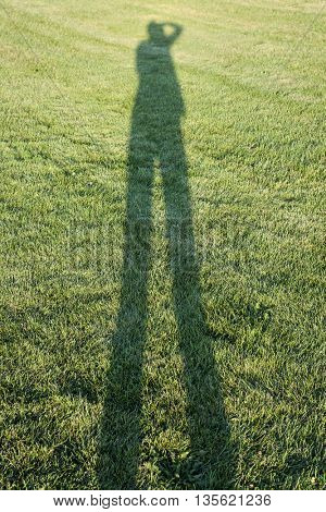 One person casting long shadow on grass lawn taking photos