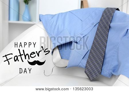 Happy father's day concept. Man's shirt with tie on chair and shelf on background