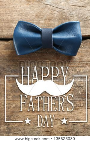 Happy father's day concept. Blue leather bow tie on a brown wooden background