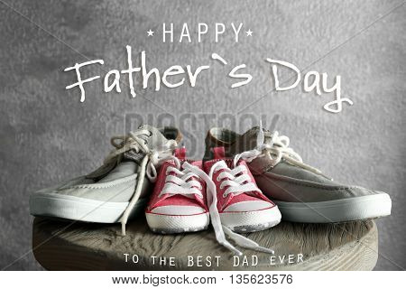 Happy father's day concept. Big and small shoes on wooden table