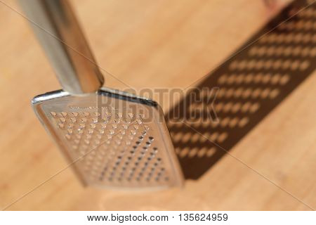 Metal grater photographed from above so it casts a shadow on the wooden chopping board. Very shallow depth of field.
