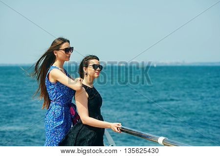 two girls posing on a background of sea landscape