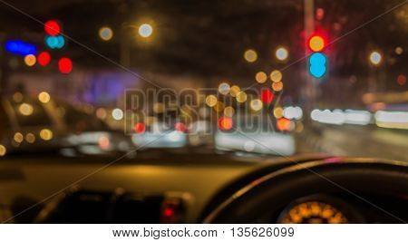 blur image of inside cars with bokeh lights from traffic jam on night time.
