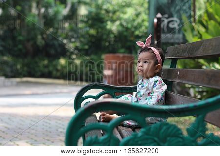 Infant seating on the bench alone watching far away