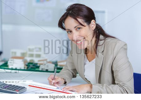 beautiful young smiling female sitting at the desk and writing