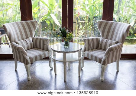 Design Of Interior Living Room With Sofa Furniture With Mirror Window And Green Garden Background