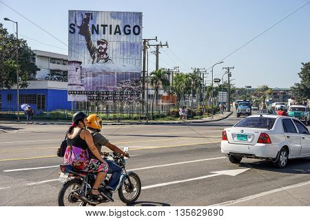 Santiago de Cuba Cuba - January 11 2016: Typical scene of one of streets in the center of Santiago de cuba - Colorful architecture people walking around and vintage american cars in the roads. Santiago is the 2nd largest city in Cuba