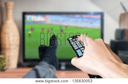 Man Is Relaxing With Legs On Table And Is Watching Football Matc