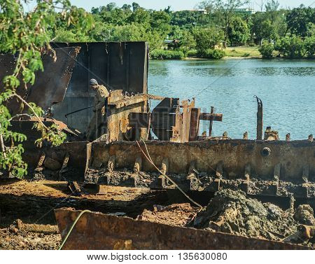 Santiago De Cuba Cuba - January 11 2016: Male working to dismantle an old rusty ship wreck. ship breaking yard. The work is carried out without any kind of safety equipment