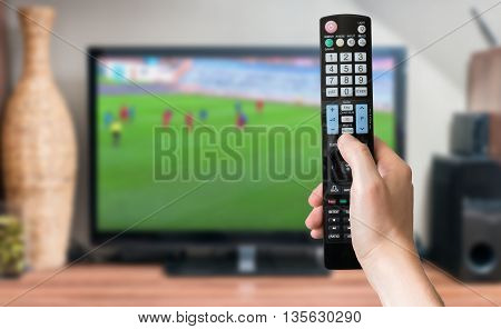 Man is relaxing with legs on table and is watching football match on tv and holds remote controller.