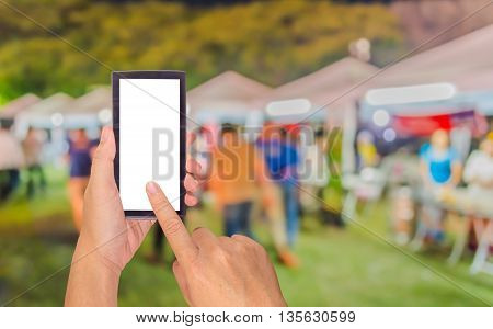 Male Hand Is Holding A Modern Touch Screen Phone And Blurred Image Of Night Festival For Background