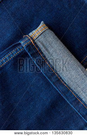 tucked trouser leg dark blue jeans closeup