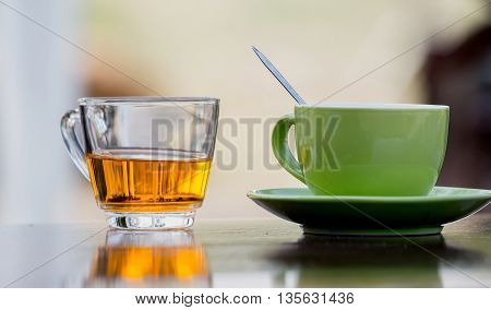 Tea glasses and green ceramic coffee mug on a wooden table.