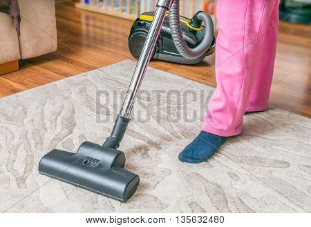 Woman Is Cleaning Carpet With Vacuum Cleaner.