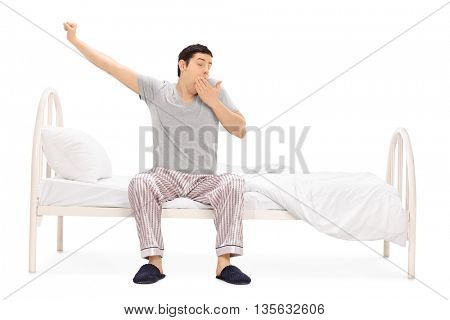 Young guy in pajamas sitting on a bed and yawning isolated on white background