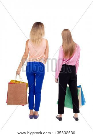 back view of  two women  with shopping bags. backside view of person.  Rear view people collection. Isolated over white background. Two girls with paper handles are close and look ahead.