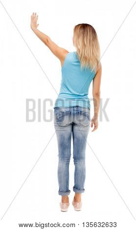 Back view of beautiful woman welcomes. Young teenager girl in jeans hand waving from.   Isolated over white background. The girl in jeans and a blue shirt with his right hand waving.
