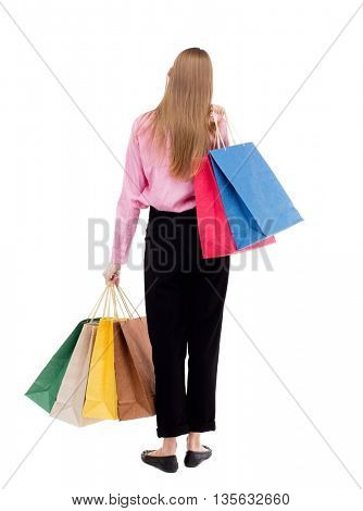 back view of woman with shopping bags . beautiful brunette girl in motion.  backside view of person.   The girl in the pink shirt is thrown over his left shoulder bags with purchases.