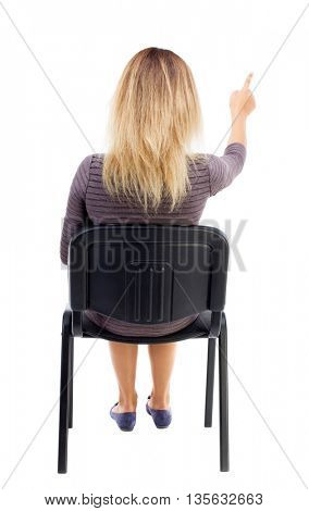 back view of young beautiful  woman sitting on chair and pointing.  girl  watching. Rear view people collection.  backside view of person.