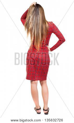 back view standing young beautiful woman. Rear view people collection.  backside view of person.  Isolated over white background. The girl in red plaid dress thoughtfully straightens hair on his head