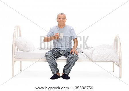 Cheerful senior sitting on his bed and holding a cup of coffee isolated on white background