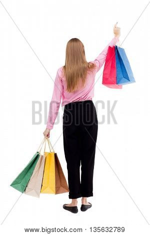 back view of woman with shopping bags . beautiful brunette girl in motion.  backside view of person.  A girl in pink shirt stands with colorful shopping bags and showing thumb up.