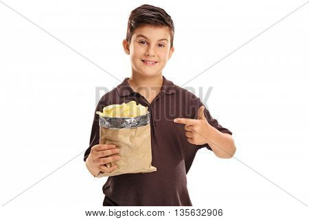 Joyful little boy holding a bag of potato chips and pointing to it with his finger isolated on white background