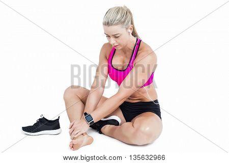 Injured female athlete sitting and touching ankle on white background