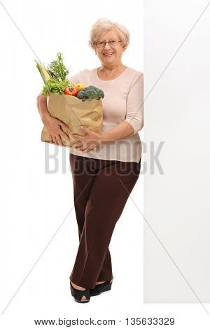 Full length portrait of a senior lady holding a bag of groceries and leaning against a wall isolated on white background