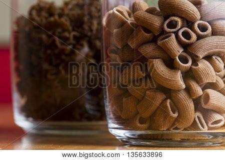 Uncooked macaroni pasta in a jar closeup