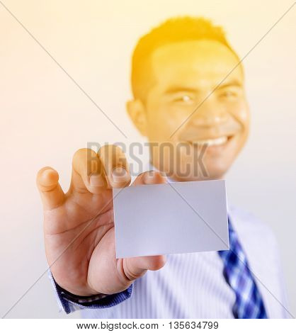 Portrait of asian Thai business man smile and showing blank white business card selective focus shallow depth of field with sunray effect