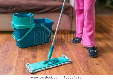 Woman Is Cleaning Wooden Floor With Mop.