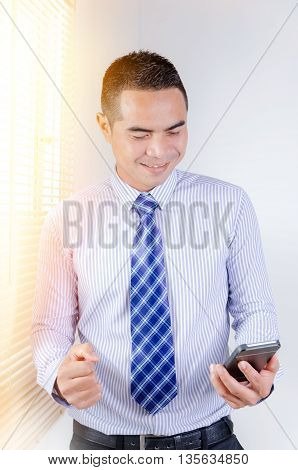 Portrait of smile asian Thai business man looking to mobile smart phone with sunray effect