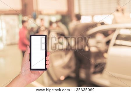 Image Of Hand Holding Smartphone And Blur Technician Fixing Car In The Garage.