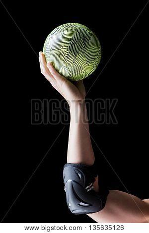Female athlete with elbow pad holding handball on black background