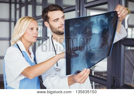 Doctor colleaguesexamining X-ray while standing at hostiptal