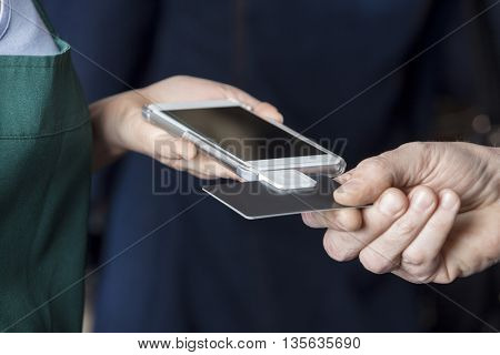 Cropped Image Of Saleswoman Accepting Card Payment From Customer