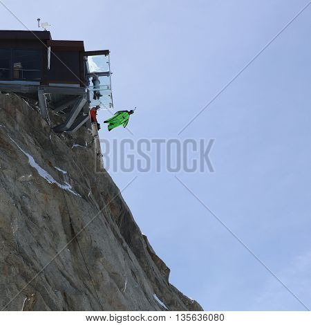 Chamonix-Mont-Blanc, France - May 20, 2016: A BASE Jumper in Wingsuit jumps from the Top of Aiguille de Midi (3842m). Beside a Couple in the new