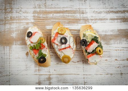 Tasty various italian sandwiches with seafood against rustic wooden background. Crostini with cheese crab sticks and sliced olives horizontal top view