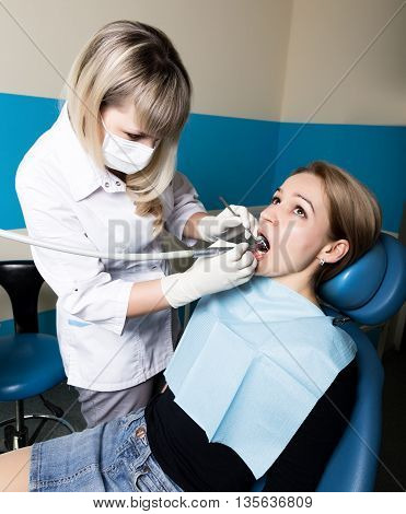 The reception was at the female dentist. Doctor examines the oral cavity on tooth decay. Caries protection. doctor puts the patient an anesthetic injection. close-up of the patient's mouth and squirt.