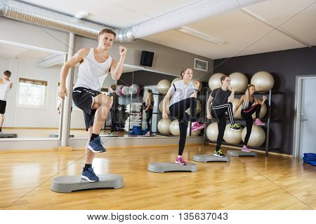 Active Men And Women Performing Step Exercise In Gym