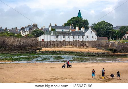 Anstruther Scotland - July 26 2012: Fife area people on the beach of the fishermen village.