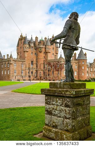 Angus Scotland - July 27 2012: Fife area the Glamis castle childhood home of the Queen Elizabeth. In the foreground the King Charles II statue.