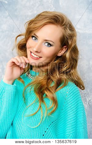 Cheerful pretty woman in a bright casual sweater looking at camera and smiling. Beauty, fashion. Bright make-up, cosmetics.