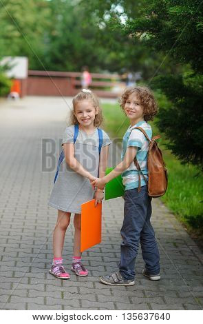 Boy and girl - pupils of elementary school. Beginning of academic year. Children hold hands and smile. Warm day of an early autumn.