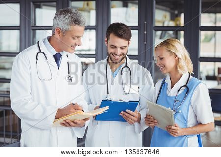 Senior doctor discussing with coworkers at hospital